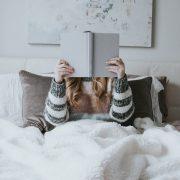 perempuan membaca buku di tempat tidur