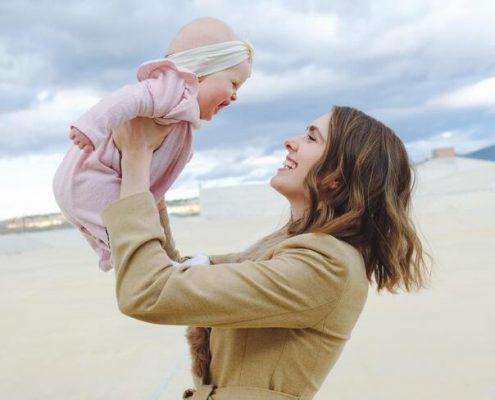 Peran Orang Tua sebagai Sumber Rasa Aman bagi Anak; gambar perempuan menggendong bayinya di udara